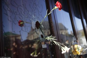 Flowers in bullet holes in the windows of the Carillon Bar, Paris